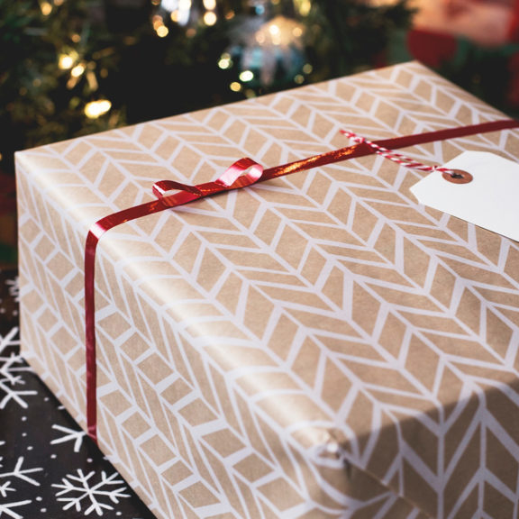 gold-and-white-gift-box-on-black-and-white-fair-isle-print-surface