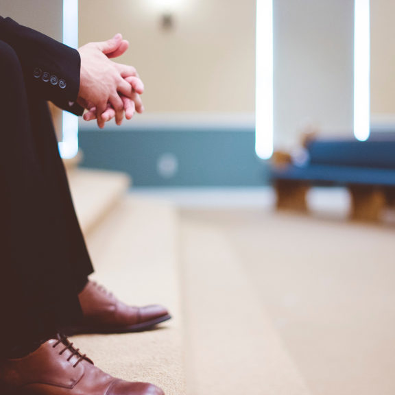 man-sitting-on-brown-carpeted-stairs-inside-church