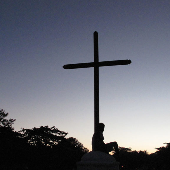 silhouette-of-person-sitting-below-cross